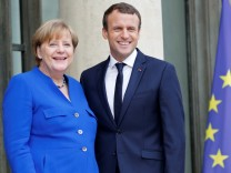 French President Emmanuel Macron arrives with German Chancellor Angela Merkel to attend a Franco-German joint cabinet meeting at the Elysee Palace in Paris