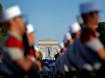 Soldiers of the French Foreign Legion are seen prior to the start of the traditional Bastille day military parade on the Champs-Elysees  with the Arc de Triomphe in the background in Paris