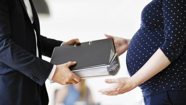 Gestellte Szene Eine schwangere Frau bekommt im Buero Aktenordner von einem Vorgesetzten ausgehaend