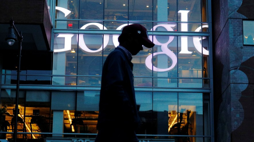 A pedestrian walks past the Google offices in Cambridge