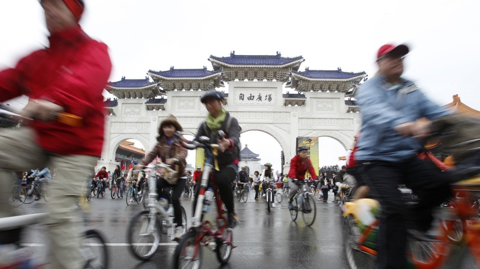 People cycle their bicycles at the Chiang Kai-shek Memorial Hall in Taipei
