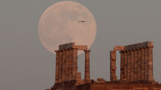 A fullmoon rises over the Temple of Poseidon, the ancient Greek god of the seas, in Cape Sounion, east of Athens