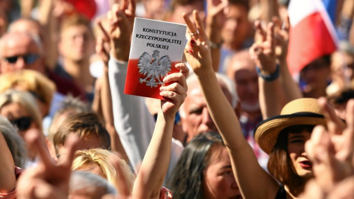 A protester holds a copy of the Polish Constitution during an opposition protest at the Market Square in Krakow