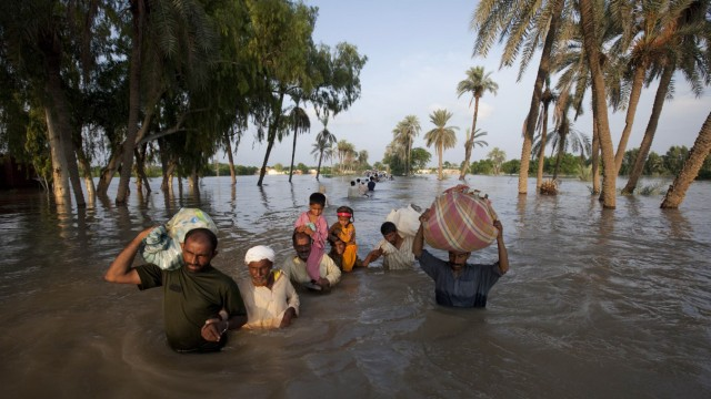 A family  wades through flood waters while evacuating Baseera, Pakistan
