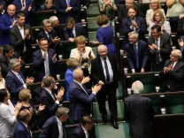 Law and Justice party leader Jaroslaw Kaczynski enters the parliament as his party members applause in Warsaw
