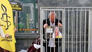 Amnesty International Belgium's Director Philippe Hensmans poses in a cage in front of the Turkish embassy in Brussels to protest against the detention of his Turkish counterpart Idil Eser