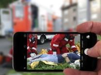 Gaffer Schaulustige fotografieren bei einem Rettungseinsatz mit der Handykamera Symbolfoto Rettu