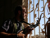 A Free Syrian Army fighter looks out through a window in rebel-held Al-Yadudah village, in Deraa Governorate, Syria