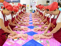People participate in a free infant care training course organized by local labor union in Haikou