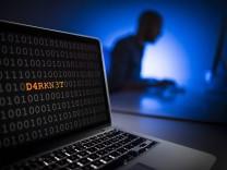 Illustration zum Thema Darknet Nahaufnahme eines Laptops mit Binaercode Im Hintergrund sitzt ein