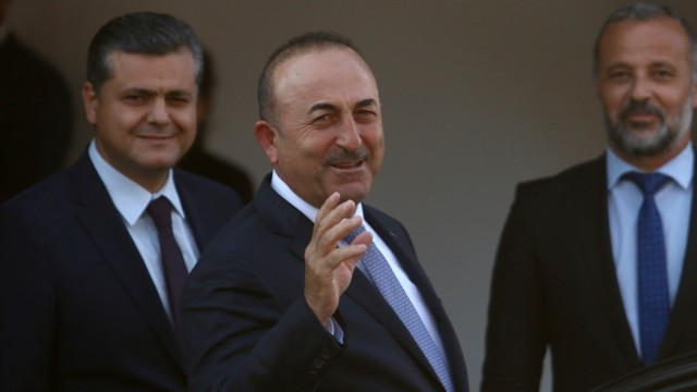 Turkey's Foreign Minister Mevlut Cavusoglu greets journalists during a visit in the Turkish Cypriot northern part of the divided city of Nicosia