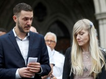 Charlie Gard's parents Connie Yates and Chris Gard read a statement at the High Court after a hearing on their baby's future, in London