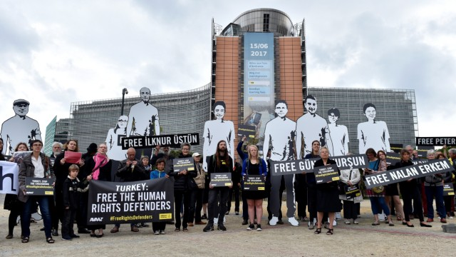 Amnesty International activists hold a protest outside the EU commission with giant figures depicting activists who were detained in Turkey, in Brussels