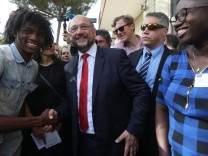 Germany's Social Democratic Party candidate for chancellor Martin Schulz is welcomed as he arrives to visit an immigration centre for unaccompanied minors in Catania