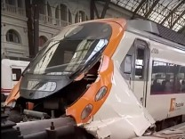 A commuter train is seen crashed into a railway buffer in Barcelona's Francia station