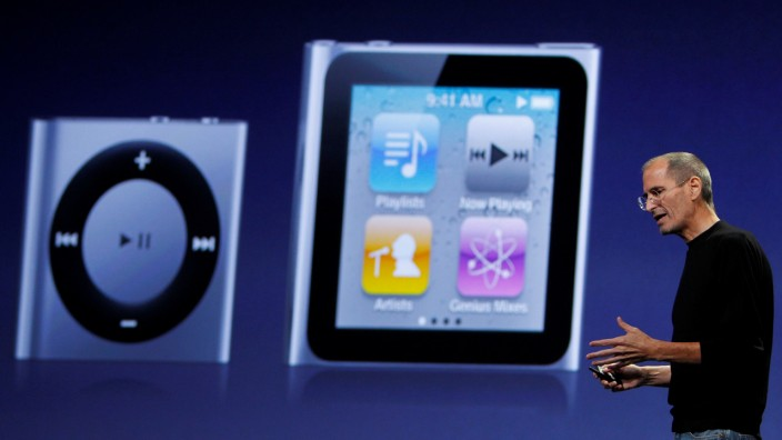 FILE PHOTO: Apple CEO Jobs speaks on stage with images of the iPod Shuffle and iPod Nano projected on screen at Apple's music-themed September media event in San Francisco
