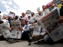 Press freedom activists read opposition newspaper Cumhuriyet during a demonstration in solidarity with the jailed members of the newspaper outside a courthouse, in Istanbul
