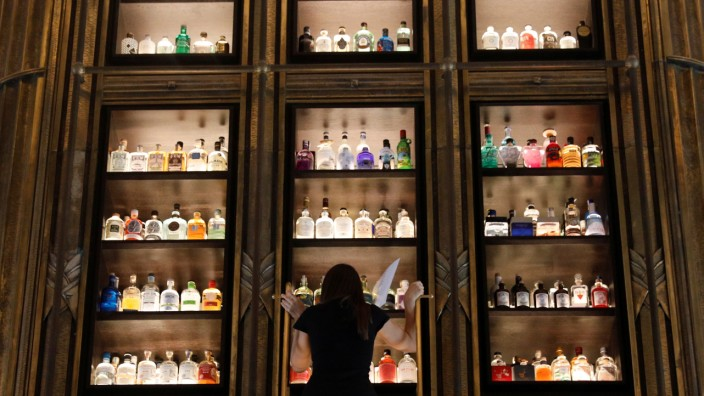 A woman climbs a ladder to reach a bottle from a collection of gin in the 'gin tower' of Atlas bar in Singapore