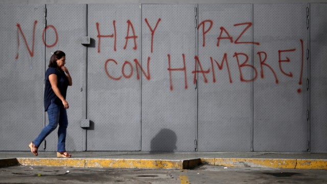A woman walks in front of a graffiti that reads 'There is no peace with hunger' during a strike called to protest against Venezuelan President Nicolas Maduro's government in Caracas
