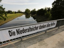 A banner hangs on a bridge over the formerly flooded Ohe river in Niederalteich, after the waters of the nearby Danube and Isar river subsided in the region's worst floods in a decade