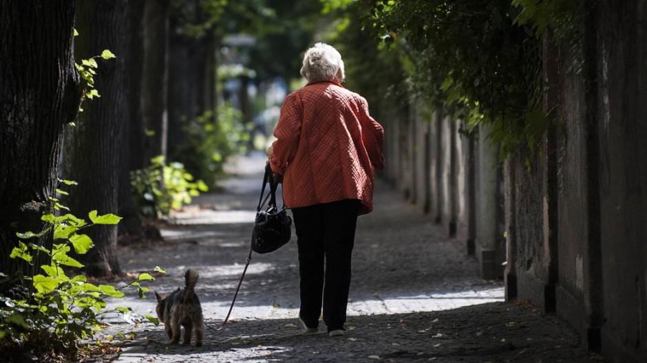 Eine Frau laeuft mit einem Hund entlang eines Gehweges in Berlin 11 08 2016 Berlin Deutschland PUB