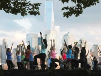 People stretch as they take part in a yoga class across the Hudson River from New York's Lower Manhattan and One World Trade Center in a park in Hoboken, New Jersey