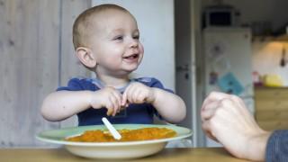 Ein Kleinkind wird mit Brei gefuettert Bonn Deutschland Mother feeds her baby Bonn Germany