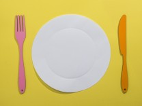 Food concept with paper plate fork and knife on yellow background PUBLICATIONxINxGERxSUIxAUTxHUNxO