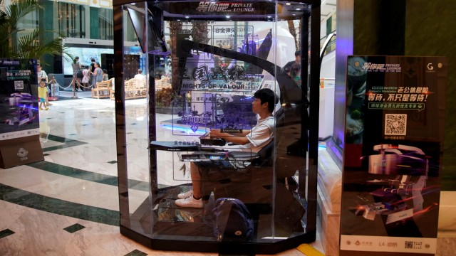 An employee demonstrates a 'husband pod' at a shopping mall in Shanghai