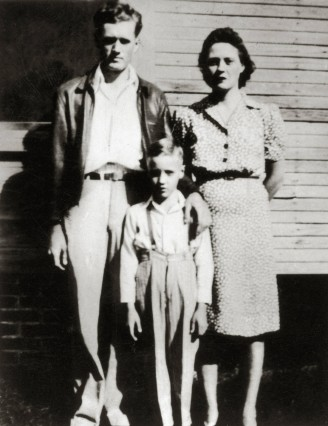 Elvis Presley with his parents Gladys Presley Vernon Presley outside of their home in Tupelo Mis