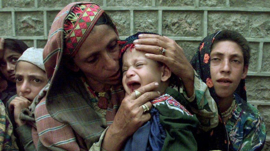 A DISPLACED MOTHER COMFORTS HER CHILD IN A CHINARI REST HOUSE IN KASHMIR