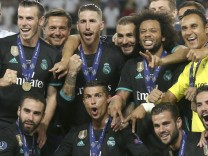 Real Madrid s players pose with the trophy after winning the UEFA Super Cup match between Real Madri