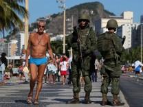 Brazilian navy soldiers patrol the Copacabana beach as part of a plan to combat organized crime in Rio de Janeiro