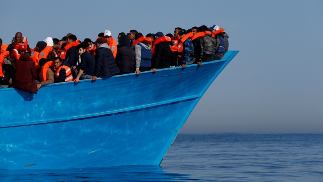 FILE PHOTO: Migrants on a wooden boat await rescue by the Malta-based NGO Migrant Offshore Aid Station (MOAS) in the central Mediterranean