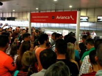 People congregate in front of counters of Avianca airline at the Simon Bolivar airport in Caracas
