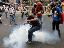 FILE PHOTO: A demonstrator prepares to throw a tear gas canister during riots at a rally against Venezuelan President Maduro's government in Caracas