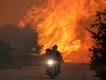 Two men and a dog on a motorbike flee a wildfire burning near the village of Varnavas