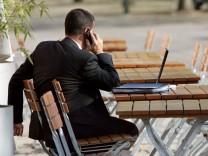 Mann mit Mobiltelefon und Laptop