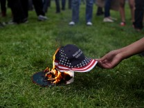A demonstrator in opposition of U.S. President Donald Trump sets a hat on fire during a 'People 4 Trump' rally in Berkeley, California