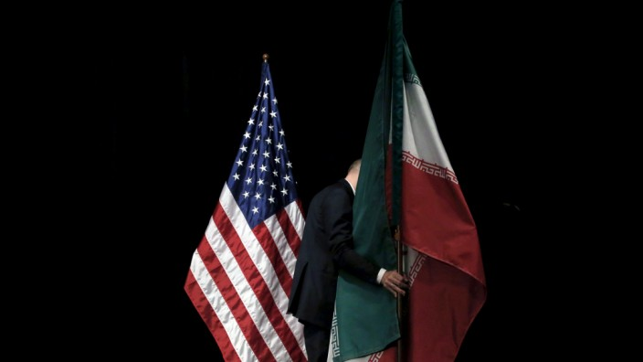FILE PHOTO: A staff member removes the Iranian flag from the stage during the Iran nuclear talks at the Vienna International Center in Vienna