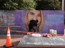 An artist works on a mural of car attack victim Heather Heyer prior to a memorial service for Heyer in Charlottesville, Virginia
