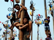 Participants react as they hold on to a greased pole during the 'Panjat Pinang' competition for the celebration of Independence Day at Ancol Dreamland Park in Jakarta
