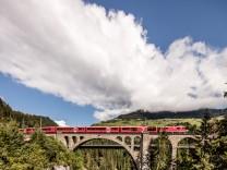 Alvra-Gliederzug mit roter Lokomotive unterwegs