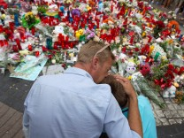People gather around an impromptu memorial two days after a van crashed into pedestrians at Las Ramblas in Barcelona
