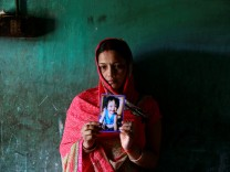 Singh holds a photo of her daughter who died in the ICU of the Baba Raghav Das hospital in Gorakhpur district