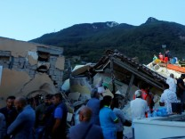 Rescue workers check a collapsed house after an earthquake hit the island of Ischia, off the coast of Naples