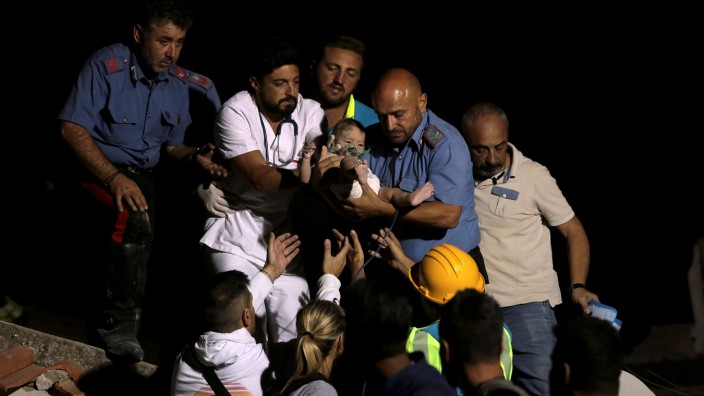 Italian Carabinieri police officer and a doctor carry a child after an earthquake hit the island of Ischia, off the coast of Naples