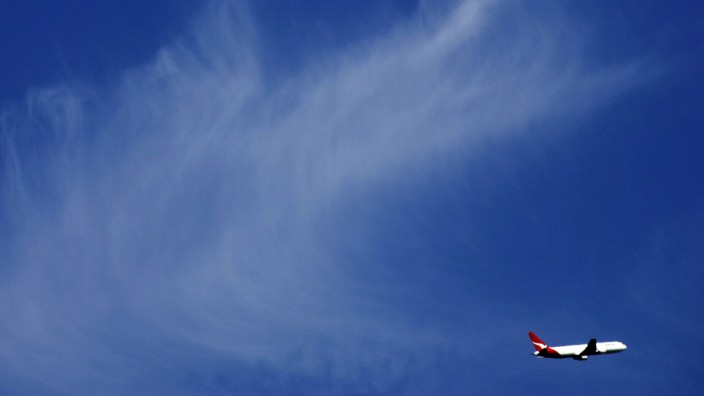File photo of a Qantas passenger plane flying past the moon above Sydney