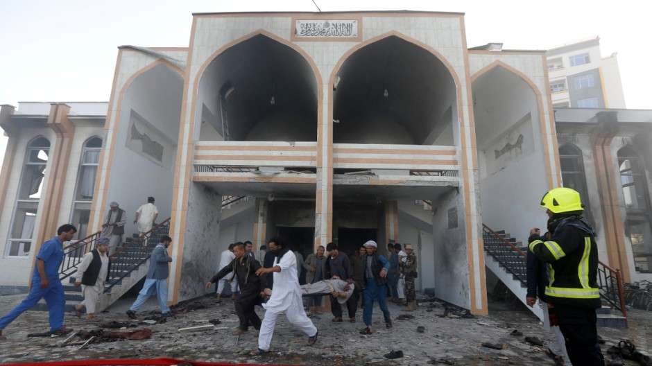 Afghan men carry a dead body from the site of a suicide attack followed by a clash between Afghan forces and insurgents after  an attack on a Shi'ite Muslim mosque in Kabul