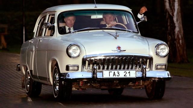File photo of Russian President Vladimir Putin sitting in the passenger seat as US President George W. Bush waves in Novo Ogarevo; FEU